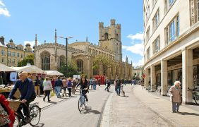 Cambridge, England - May 28, 2015: People biking at the Market square near by St. Marys church in Cambridge