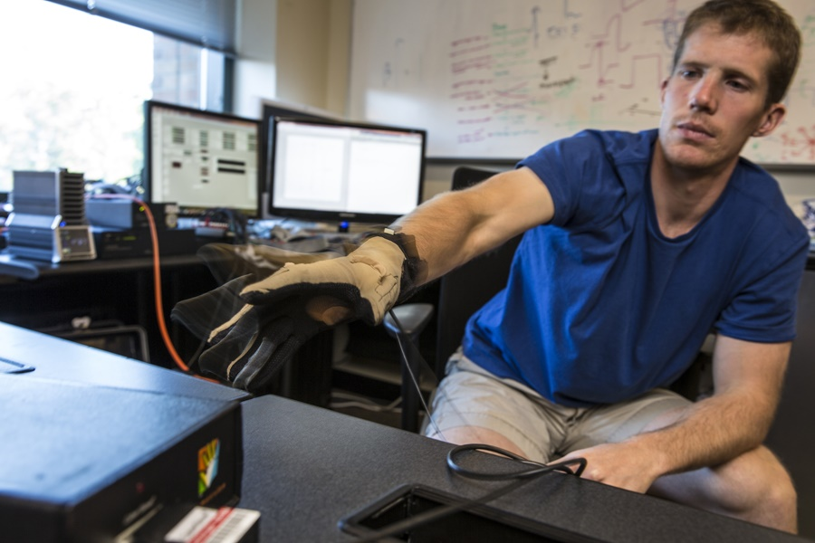 GRIDLab member David Caldwell tests the hardware used for stimulating and recording a patient's brain surface, along with a cyber glove to track the hand's movement. Mark Stone/University of Washington